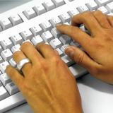 Hände schreiben auf einer Tastatur